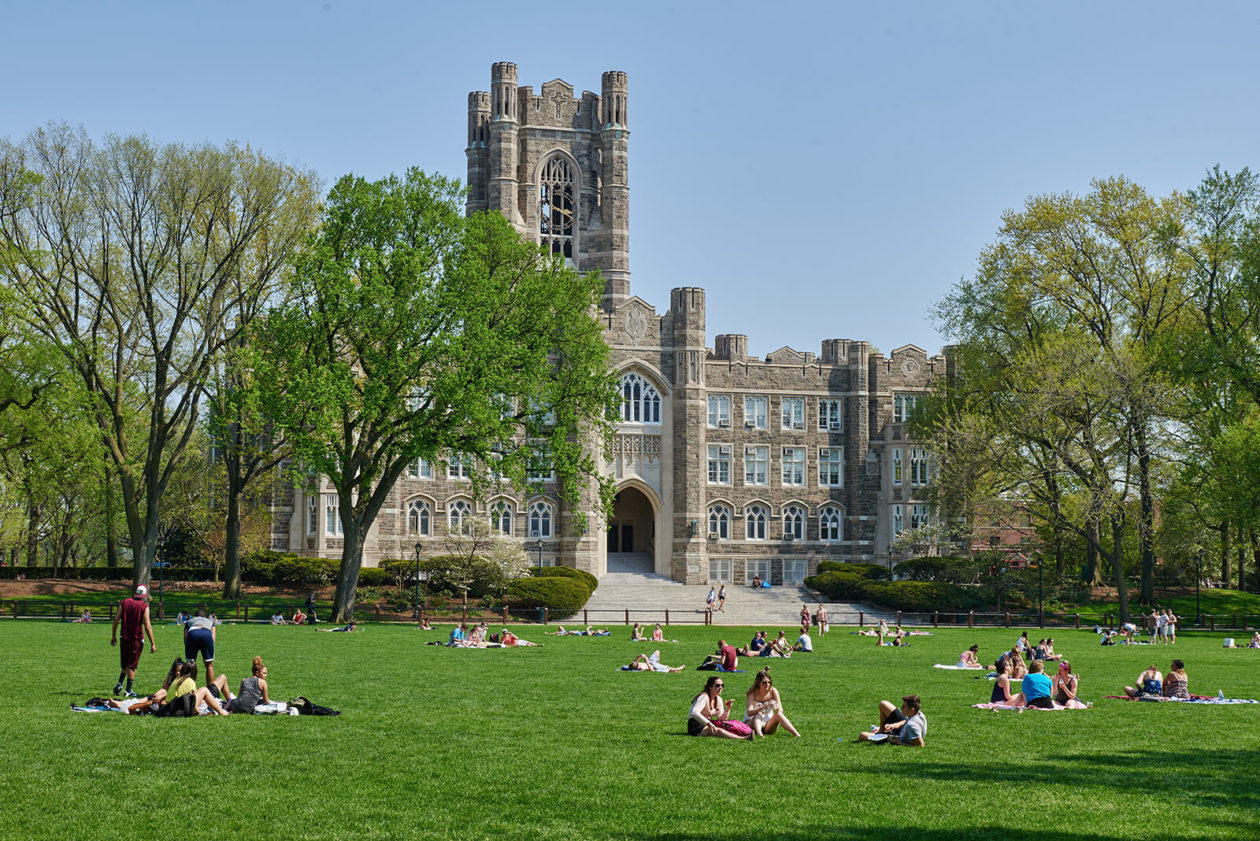 Old stone building with students outside lounging on a green lawn.